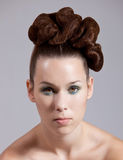 Elaborate hairstyle. Beautiful young woman with stylish hair on grey background Royalty Free Stock Images