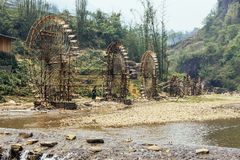 Elaborate water wheels made from bamboo with trees in the background in summer at Cat Cat Village in Sa Pa, Vietnam.  Royalty Free Stock Photo