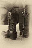 Elaborately Stitched Cowboy Boots by Chair. Elaborately stitched cowboy boots on carpet next to a chair. Photographed in black and white with a sepia tone to royalty free stock photo