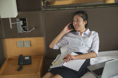 Elaborazione multitask della donna di affari nel suo letto, sul sorridere del telefono Fotografia Stock