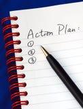 Elabori il piano d'azione in un rilievo di scrittura Fotografie Stock Libere da Diritti