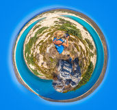 Elafonisos Island planet. Little planet composition of an aerial view of a young woman with blue sarong photographing the blue sea of Simos Beach, Elafonisos Stock Photo