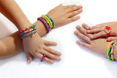Elastic and colorful rainbow loom bracelet on hands. Colorful bracelets and jewelry with rubber bands rainbow loom on girls hands royalty free stock photo
