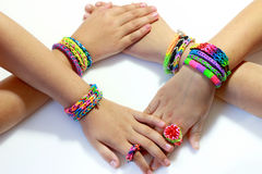 Elastic and colorful rainbow loom bracelet on hands. Colorful bracelets and rings with rubber bands rainbow loom on girls hands stock photo