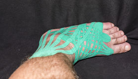 Elastic therapeutic tape left foot injury to the patient. Royalty Free Stock Images