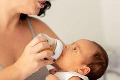 Elasticità della madre bere il bambino infantile dell'acqua dalla bottiglia fotografie stock libere da diritti