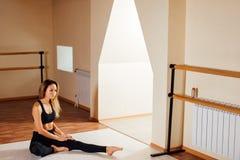 Elastyczna kobieta rozciąga ona prawa noga w gym zdjęcia stock