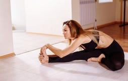 Elastyczna młoda kobieta rozciąga ona prawa noga w gym obraz royalty free