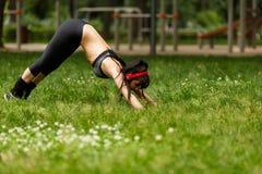Elastyczna sportowa młoda kobieta z hełmofonami robi rozciąganiu na trawie Fotografia Royalty Free