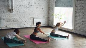 Elastyczne dziewczyny robią joga ćwiczy szeroki kąt sadzającego przedniego chył w loft stylu studiu z białymi ścianami i ampułą zbiory
