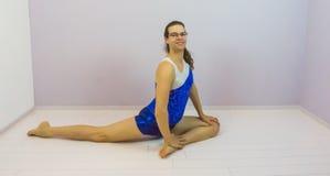 Elastyczny akrobatyczny gimnastyczki obsiadanie w połówki rozszczepiony uśmiechniętym i patrzeć w kamerze zdjęcia stock
