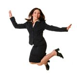 Elated businesswoman. Woman in black business suit jumps for joy; isolated on white background Royalty Free Stock Images