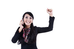Elated businesswoman using cell phone. Businesswoman expresses her joy while using her cell phone Royalty Free Stock Image