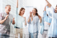 Elated cheerful colleagues standing in the office. On the edge of delight. Cheerful gald colleagues standing in the office and feeling happy while working in one royalty free stock image