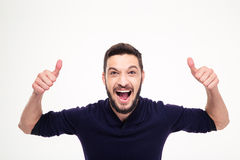 Elated excited young happy man shouting and showing thumbs up. Elated excited young happy man with beard shouting and showing thumbs up with both hands over Royalty Free Stock Image