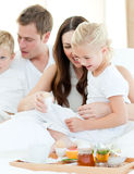 Elated family having breakfast sitting on bed. At home Stock Photos