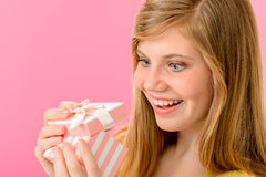 Elated girl opening gift. Isolated on pink background Royalty Free Stock Photo