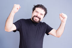 Elated man with fists held up. Single handsome bearded man in black shirt holding fists up with elated expression over gray background Royalty Free Stock Photo