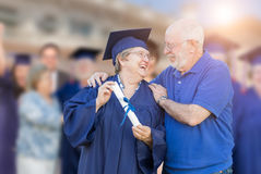 Elated Senior Adult Woman In Cap and Gown Being Congratulated By Husban Royalty Free Stock Photos