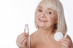 Elated senior woman holding lotion and a cotton pad. Cosmetic products. Elated happy elderly woman holding a cleansing lotion and a cotton pad and smiling while Royalty Free Stock Image