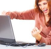Elated woman with laptop. A woman clenches her fists, smiling in elation as she looks at the screen of her laptop computer Royalty Free Stock Photo