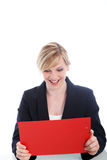 Elated woman reading notes on a clipboard. Elated young business woman reading notes on a clipboard with a look of surprised pleasure isolated on white with Stock Photo