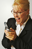 Elated Woman Using Cell Phone. Businesswoman expresses her joy while using her cell phone Royalty Free Stock Image