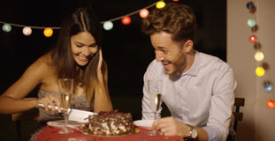 Elated young couple joking as they cut the cake Royalty Free Stock Photos