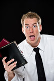 Elated young man holding bibles Royalty Free Stock Photos
