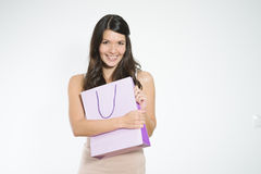 Elated young woman clutching her purchases. In a pretty purple shopping bag close to her chest in a possessive manner as she smiles happily showing her Stock Photos