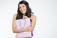 Elated young woman clutching her purchases. In a pretty purple shopping bag close to her chest in a possessive manner as she smiles happily showing her Royalty Free Stock Image