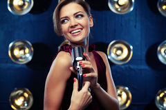 Elated young woman singing in a silver vintage microphone wearing vinous evening dress. Close-up of elated young woman singing in a silver vintage microphone stock photos