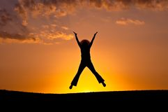 Elation jump. Silhouette. Female silhouette in a jump of elation on a background of a sunset Royalty Free Stock Images