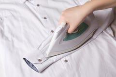 Żelazo w żeńskim ręki prasowania rękawie bawełniana koszula zdjęcie stock