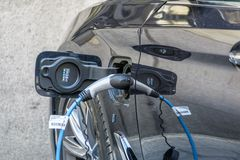 Elbil som laddar batteriet med en kabel från en elektricitetsbensinstation fotografering för bildbyråer