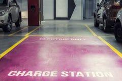 Elbiluppladdningsstation i underjordisk inomhus parkering av gallerian eller kontorsbyggnad Reserverad parkeringsplats f?r milj? arkivfoto