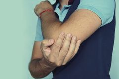 Elbow bone fracture. male having pain in injured arm royalty free stock photo