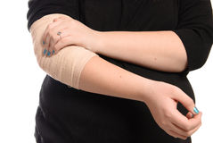 Elbow Injury. A young girl is holding her elbow which is wrapped in a tensor bandage, isolated against a white background Royalty Free Stock Images