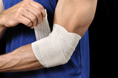 Elbow injury. Closeup of athletic man tending injured elbow with sports wrap on black background Royalty Free Stock Images