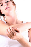 Elbow In Pain. A young woman is holding her elbow in pain. This is a highkey image Stock Images