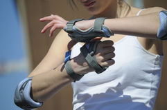 Elbow and palm pads. Young girl puts on elbow and palm pads Stock Image