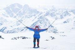Elbrus, een bergbeklimmer op het stijgen, hief omhoog de trekkingspolen op stock foto