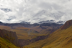 Elbrus mountain Caucasus. Snow-capped Elbrus mountain surrounded by clouds rises above the mountain area in Kabardino-Balkaria Caucasus, Russia. Photo has been Stock Image