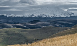 Elbrus mountain Caucasus. Snow-capped Elbrus mountain surrounded by clouds rises above the mountain area in Kabardino-Balkaria Caucasus, Russia. Photo has been Royalty Free Stock Photo