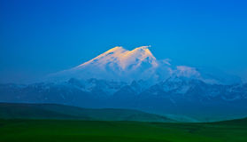 Elbrus mountain lit by the rays of the rising sun Stock Images