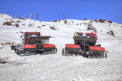 Elbrus. Snow grooming on the slope of mountain. CAUCASUS, RUSSIA - May 01.2015: Snow grooming with passengers in a basket goes by the second level of mountain royalty free stock photos