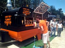 A man watching the tasty hamburger goods shown at a show case of a orange food truck royalty free stock photo