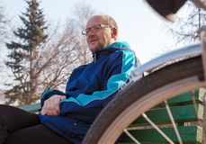 Eldely man sitting on a bench near his bicycle in a city park Royalty Free Stock Photo