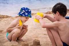 The elder brother helps his younger brother build from the sand on the seashore. Stock Photo