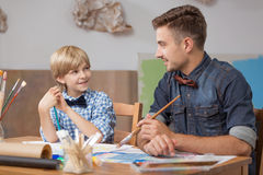 Elder brother painting with sibling Royalty Free Stock Photo